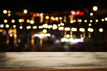Hintergrundbild von Holztisch vor abstrakten verschwommenen Restaurantlichtern