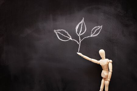 business concept of wooden figure with drawn small plant on blackboard. growth, teaching and vision metaphor Banco de Imagens - 131835173