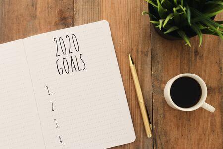 Geschäftskonzept der Top View 2020-Zielliste mit Notebook, Tasse Kaffee über Holzschreibtisch Standard-Bild