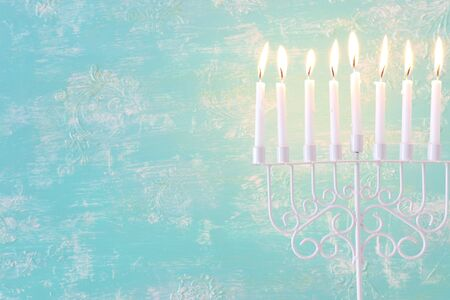 Religion image of jewish holiday Hanukkah background with menorah (traditional candelabra) and candles over pastel blue background Stock Photo