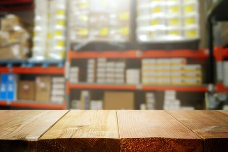warehouse background, wooden empty table and blurred storage shelfs. Ready for mock up or product display industry