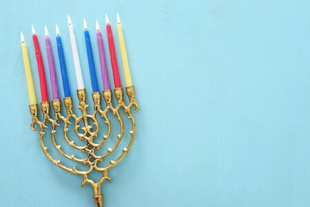 Religion image of jewish holiday Hanukkah background with menorah (traditional candelabra) and candles over pastel blue background. top view, flat lay