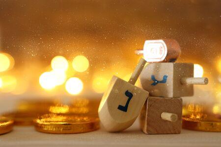 Concepto de religión de la festividad judía de Hanukkah con dreidels de madera (peonza) y monedas de chocolate sobre mesa de madera y fondo de luces bokeh