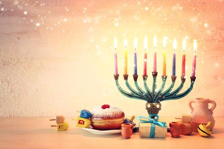 religion image of jewish holiday Hanukkah background with menorah (traditional candelabra), spinning top and doughnut Stock Photo