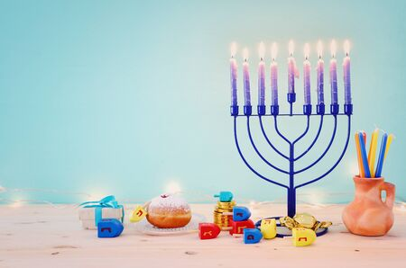 religion image of jewish holiday Hanukkah background with menorah (traditional candelabra), spinning top and doughnut over pastel background