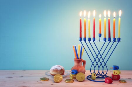 religion image of jewish holiday Hanukkah background with menorah (traditional candelabra), spinning top and doughnut