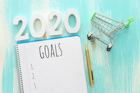 Business concept of top view 2020 goals list with notebook over wooden desk Stock Photo