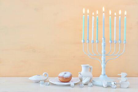 Religionsbild des jüdischen Feiertags Chanukka-Hintergrund mit Menora (traditioneller Kandelaber), Kreisel und Donut Standard-Bild