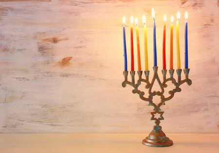 Religion image of jewish holiday Hanukkah background with menorah (traditional candelabra) and colorful candles Stock Photo