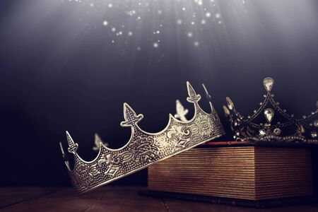 low key image of beautiful queen/king crown over old book and wooden table. vintage filtered. fantasy medieval period Banque d'images