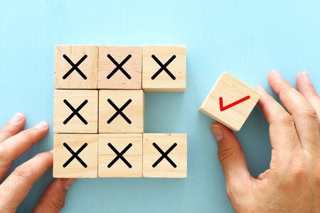 Een hand kiest een kubus met vinkje in plaats van kubussen met kruisteken. Een idee van positief denken en verandering van geest