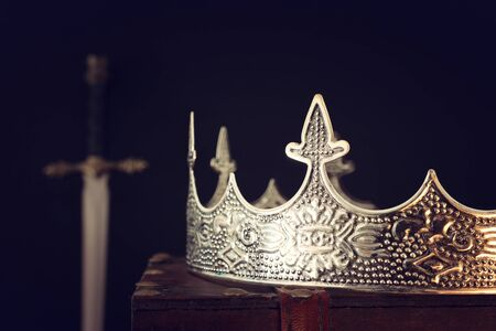 low key image of beautiful queenking crown over antique box next to sword. fantasy medieval period. Selective focus