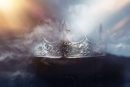 mysterious and magical photo of of beautiful queenking crown over gothic snowy dark background. Medieval period concept