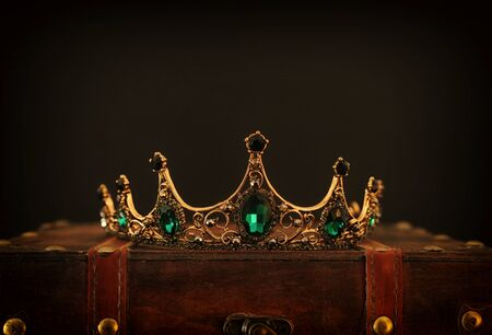 low key image of beautiful queenking crown over wooden table. vintage filtered. fantasy medieval period