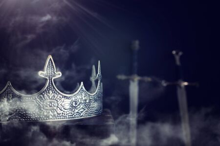 low key image of beautiful queenking crown over antique book next to sword. fantasy medieval period. Selective focus. mist and fog Stock fotó