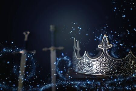 low key image of beautiful queenking crown over antique book next to sword. fantasy medieval period. Selective focus. Glitter sparkle lights