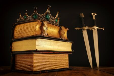 low key image of beautiful queenking crown over antique book and sword. fantasy medieval period. Selective focus Stock fotó