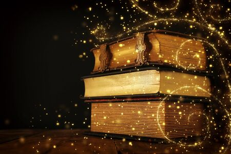 stack of antique books on old wooden table. fantasy medieval period and religious concept. Glitter sparkle lights