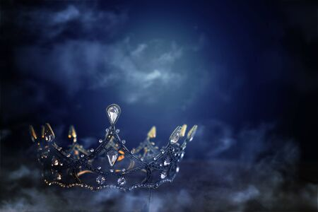 low key image of beautiful queenking crown over wooden table. vintage filtered. fantasy medieval period. mist and fog