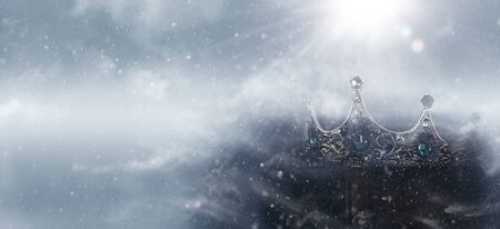 mysterious and magical photo of of beautiful queenking crown over gothic snowy black background. Medieval period concept