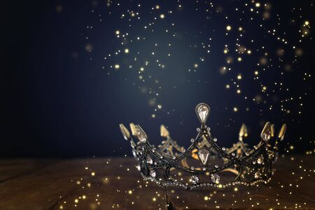 low key image of beautiful queenking crown over wooden table. vintage filtered. fantasy medieval period. Glitter sparkle lights