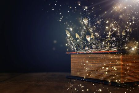 low key image of beautiful queenking crown over old book and wooden table. vintage filtered. fantasy medieval period. Glitter sparkle lights