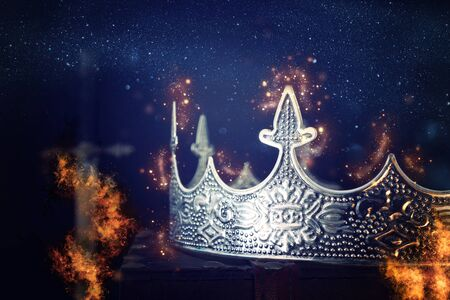 low key image of beautiful queenking crown over antique box next to sword. fantasy medieval period. Selective focus. Glitter sparkle lights ans flames fire