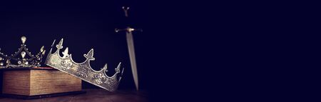 low key image of beautiful queenking crown over antique book next to sword. fantasy medieval period. Selective focus