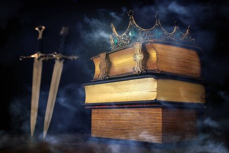 low key image of beautiful queenking crown over antique book and sword. fantasy medieval period. Selective focus. mist and fog