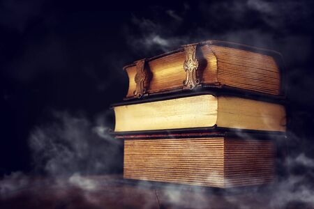 stack of antique books on old wooden table. fantasy medieval period and religious concept. mist and fog Stock fotó