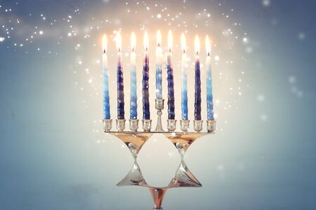 Religion image of jewish holiday Hanukkah background with david star menorah (traditional candelabra) and candles