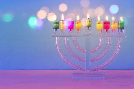 image of jewish holiday Hanukkah background with crystal menorah (traditional candelabra) and colorful oil candles Stock Photo