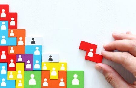 Imagen del concepto de negocio de bloques de rompecabezas de tangram con iconos de personas sobre mesa de madera, concepto de gestión y recursos humanos Foto de archivo