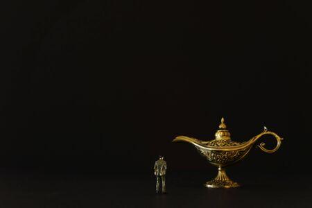Konzeptbild eines Geschäftsmannes, der eine Aladdin-Lampe mit Rauch betrachtet und um einen Wunsch bittet