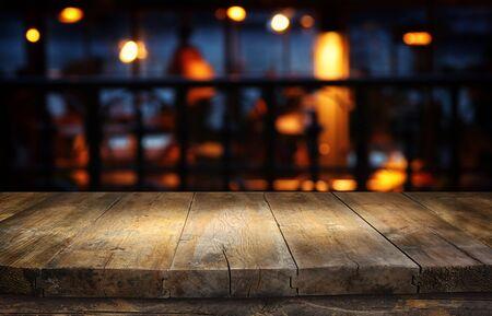 tło Obraz drewnianego stołu przed abstrakcyjnymi niewyraźnymi światłami restauracji