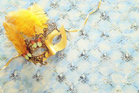 Gold elegant traditional venetian mask over vintage wooden background