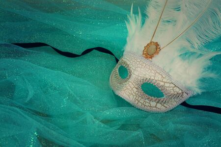 Photo of elegant and delicate white Venetian mask over mint chiffon background