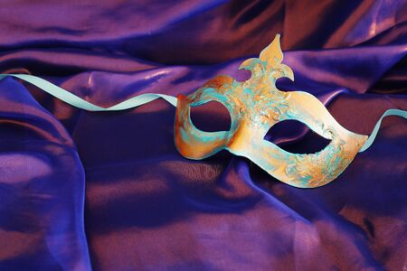Photo of elegant and delicate blue and bronze Venetian mask over purple silk background