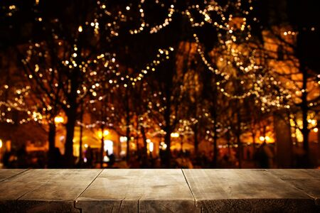 background Image of wooden table in front of street abstract blurred lights view Reklamní fotografie