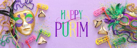 Purim celebration concept (jewish carnival holiday) over purple wooden background. Top view, Flat lay