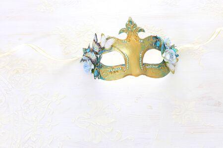 Photo de masque vénitien d'or élégant et délicat sur fond de bois blanc Banque d'images