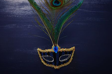 Photo of elegant and delicate blue Venetian mask with beautiful peacock feathers over dark wooden background