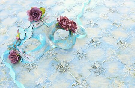 Photo of elegant and delicate blue Venetian mask over pastel wooden background