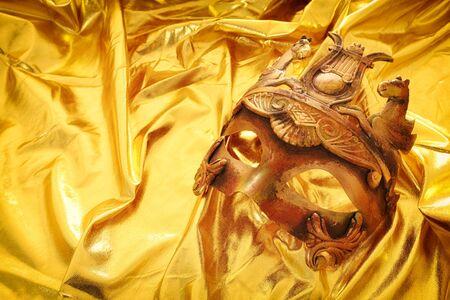 Foto einer eleganten und zarten venezianischen Maske über goldenem Seidenhintergrund