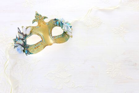 Photo of elegant and delicate gold Venetian mask over white wooden background