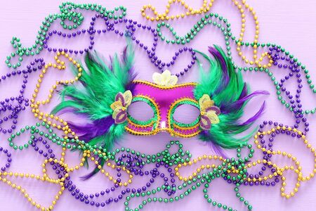 Holidays image of mardi gras masquarade venetian mask over purple background. view from above