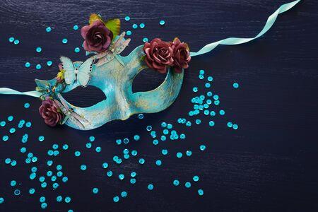 Photo of elegant and delicate blue Venetian mask over dark wooden background