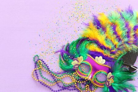 Holidays image of mardi gras masquarade, venetian mask and fan over purple background. view from above Stock Photo