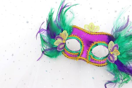 Photo of elegant and delicate Venetian mask over white chiffon background