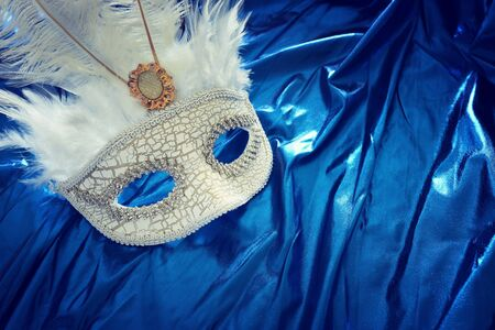 Photo of elegant and delicate Venetian mask over blue silk background Stock Photo